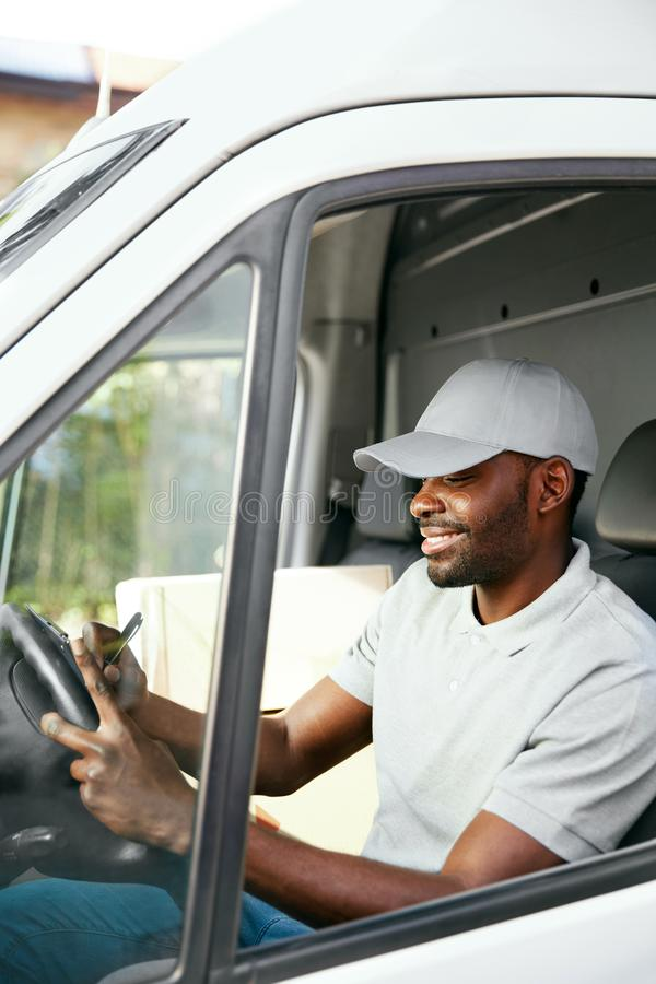 Courier. Delivery Man Reading Addresses Sitting In Delivery Van. Black Male Worker Filing Documents In Car. High Resolution royalty free stock image