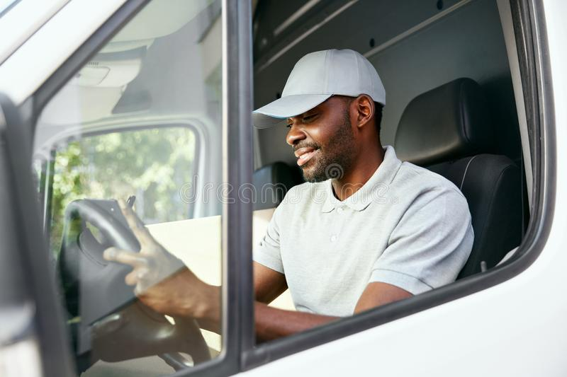 Courier. Delivery Man Reading Addresses Sitting In Delivery Van. Black Male Worker Filing Documents In Car. High Resolution stock image