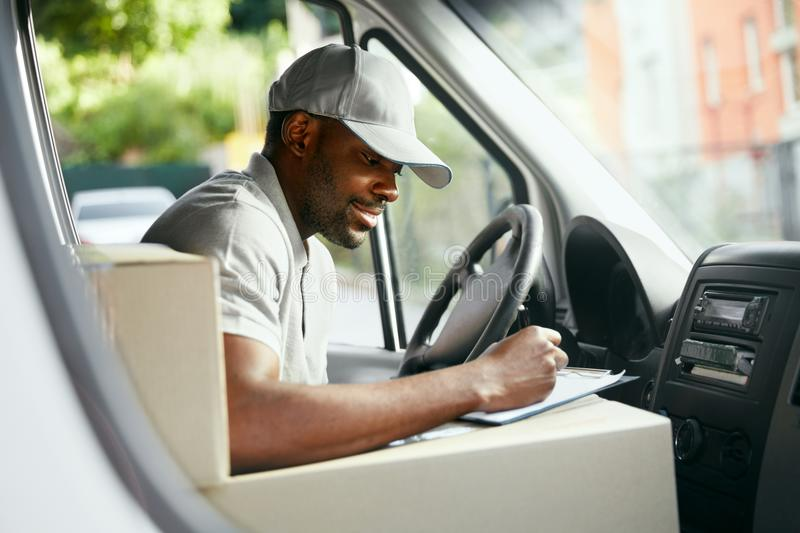 Courier. Delivery Man Reading Addresses Sitting In Delivery Van. Black Male Worker Filing Documents In Car. High Resolution royalty free stock photos
