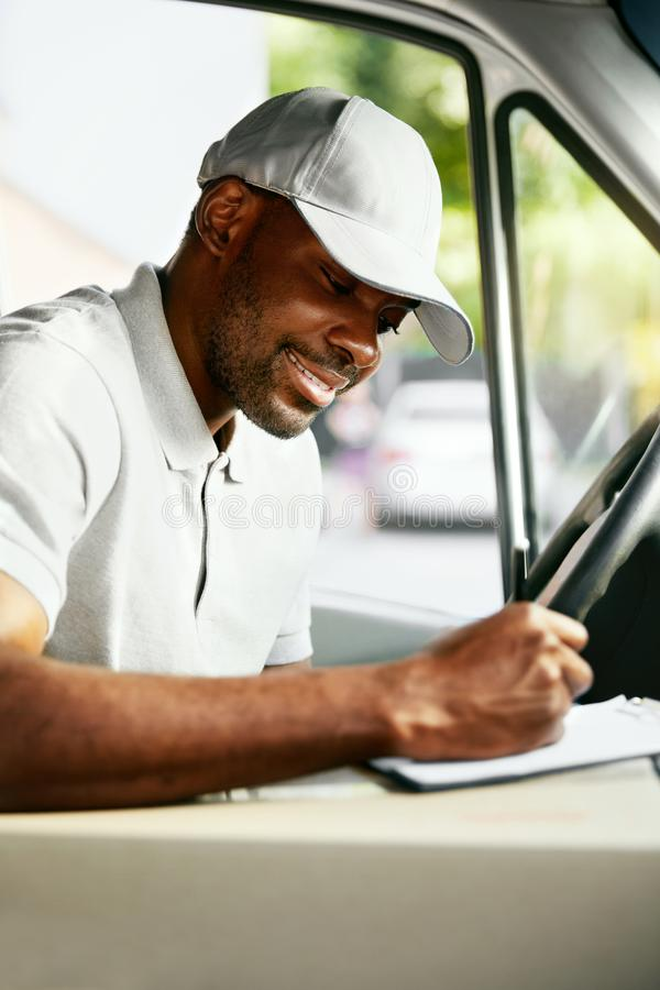 Courier. Delivery Man Reading Addresses Sitting In Delivery Van. Black Male Worker Filing Documents In Car. High Resolution royalty free stock images