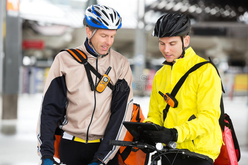 Courier Delivery Men. Two young courier delivery men in protective gear with bicycles using digital tablet royalty free stock photos