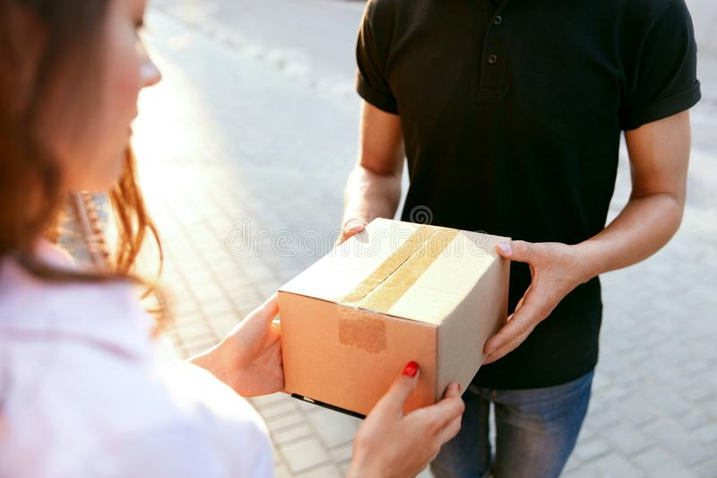 Courier Delivery Service. Closeup Hands Receiving Package. Courier Delivery Service. Closeup Of Woman`s Hands Receiving Package From Delivery Man. High stock photos