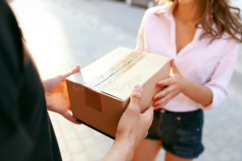 Courier Delivery Service. Closeup Hands Receiving Package. Courier Delivery Service. Closeup Of Woman`s Hands Receiving Package From Delivery Man. High stock images