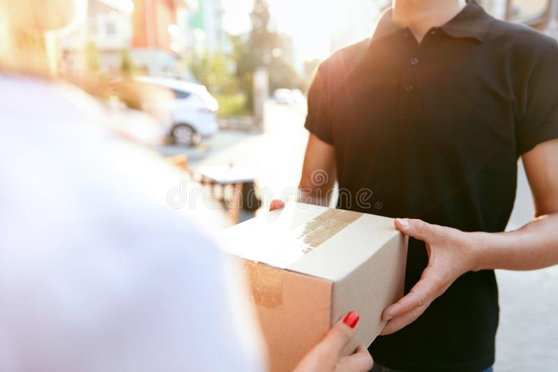Courier Delivery Service. Closeup Hands Receiving Package. Courier Delivery Service. Closeup Of Woman`s Hands Receiving Package From Delivery Man. High stock image