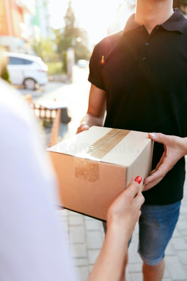 Courier Delivery Service. Closeup Hands Receiving Package. Courier Delivery Service. Closeup Of Woman`s Hands Receiving Package From Delivery Man. High stock photography