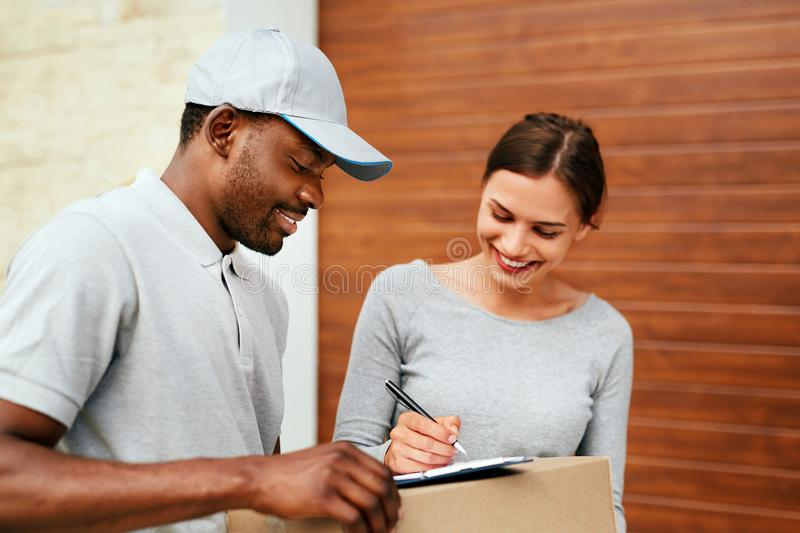 Courier Delivery Service. Man Delivering Package To Woman. Signing Documents On Box. High Resolution royalty free stock photography