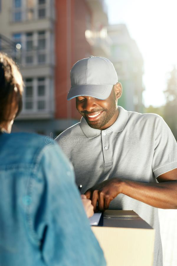 Courier Delivery Service. Man Delivering Package To Woman. Signing Documents On Box. High Resolution royalty free stock photo
