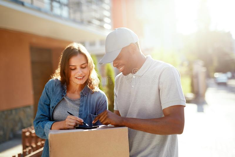 Courier Delivery Service. Man Delivering Package To Woman. Signing Documents On Box. High Resolution stock image