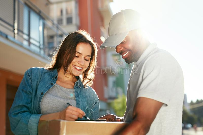 Courier Delivery Service. Man Delivering Package To Woman. Signing Documents On Box. High Resolution royalty free stock photos