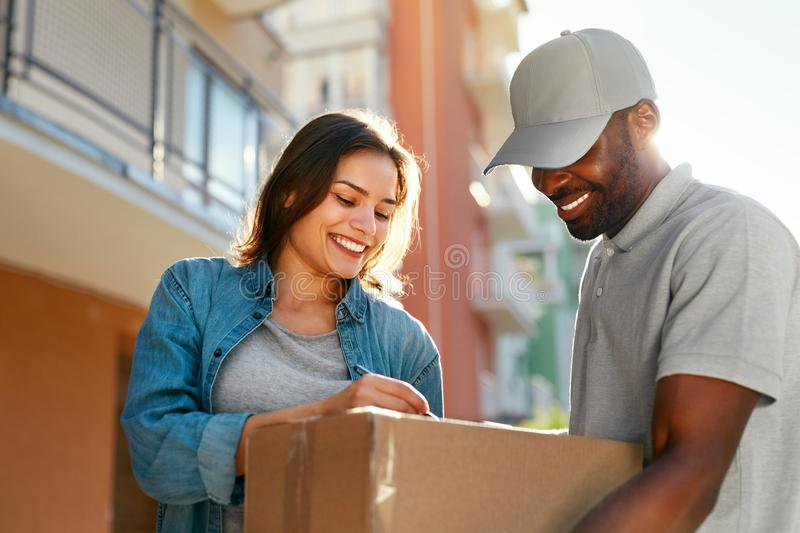 Courier Delivery Service. Man Delivering Package To Woman. Signing Documents On Box. High Resolution royalty free stock images