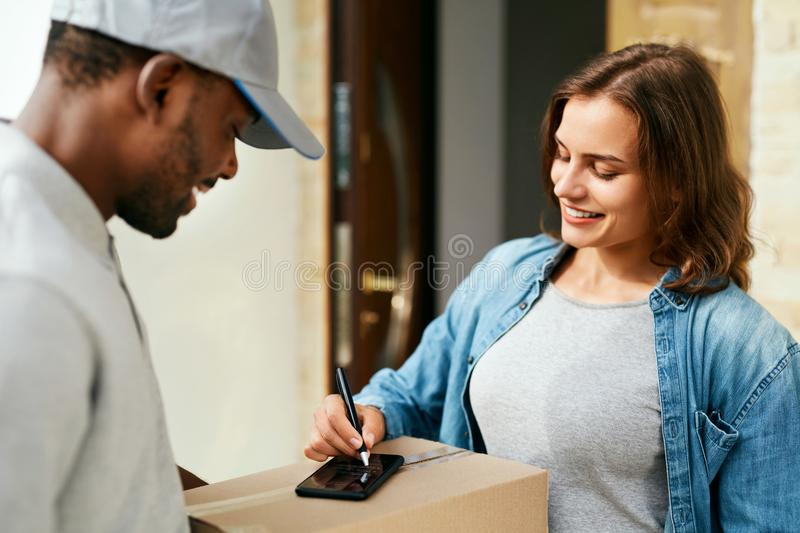 Courier Delivery Service. Man Delivering Package To Woman. Signing Documents On Box. High Resolution stock images