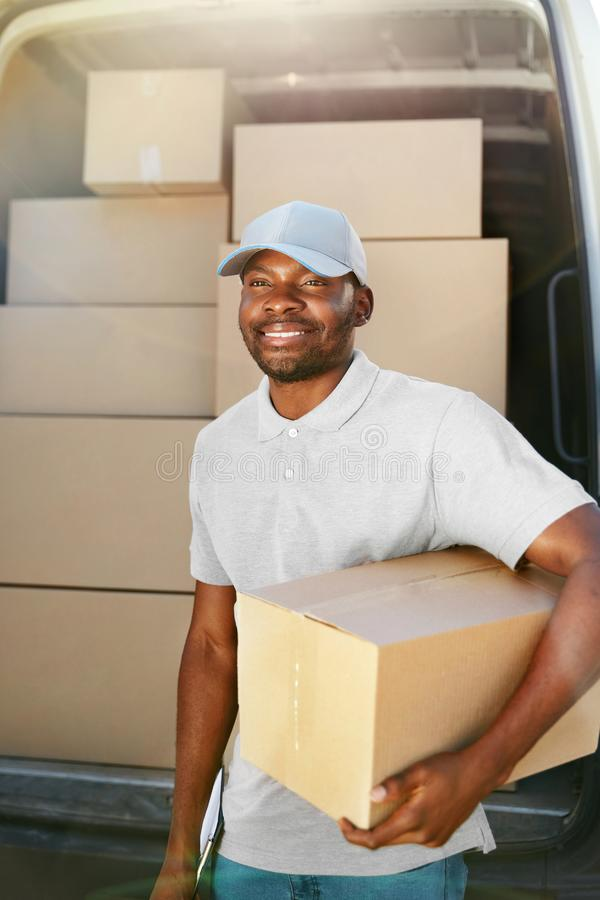 Courier Delivery Service. Man With Package Near Car With Boxes. Courier Delivery Service. Portrait Of Black Man Delivering Package Near Car With Boxes Outdoors royalty free stock images