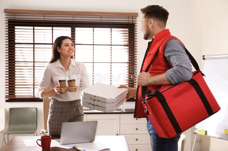 Courier giving order to young woman in office. Food delivery stock photos