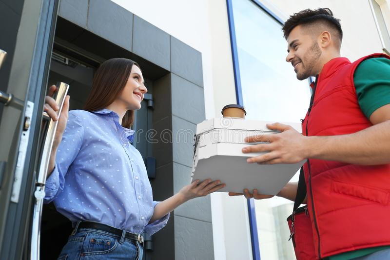 Courier giving order to young woman at open door royalty free stock photos