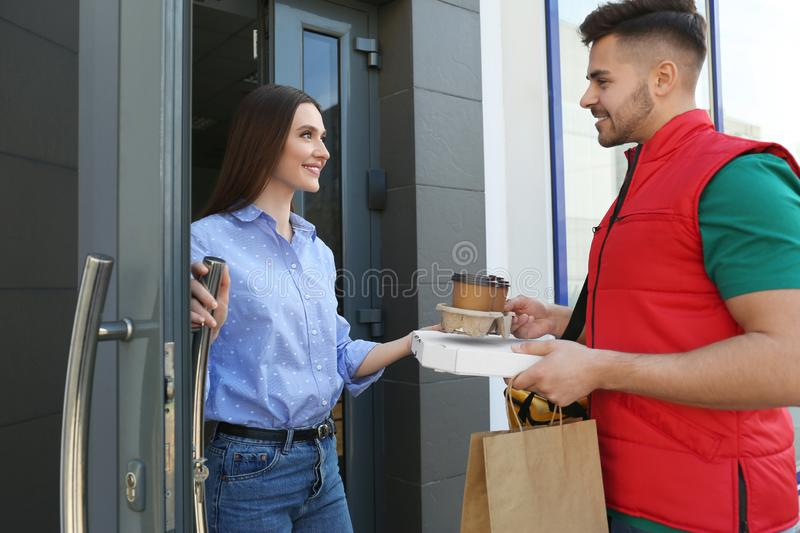 Courier giving order to young woman at open door stock image