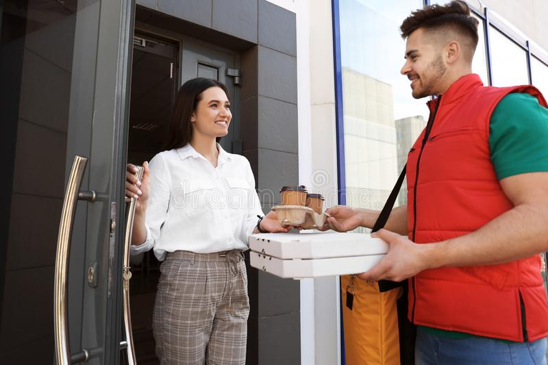 Courier giving order to young woman at open door royalty free stock photography