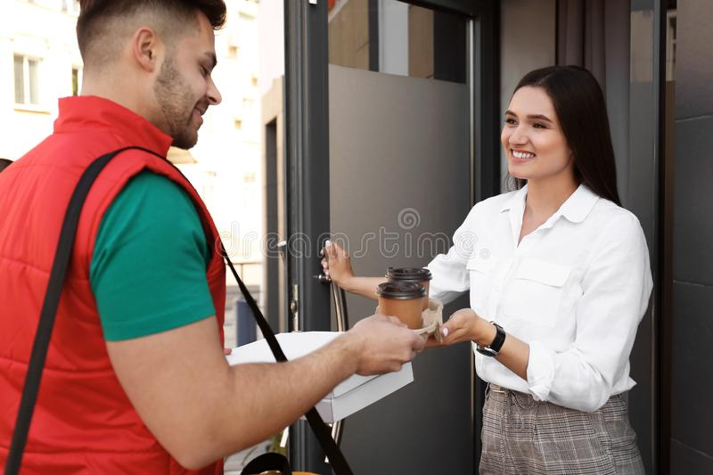 Courier giving order to young woman at open door. Food delivery stock photo