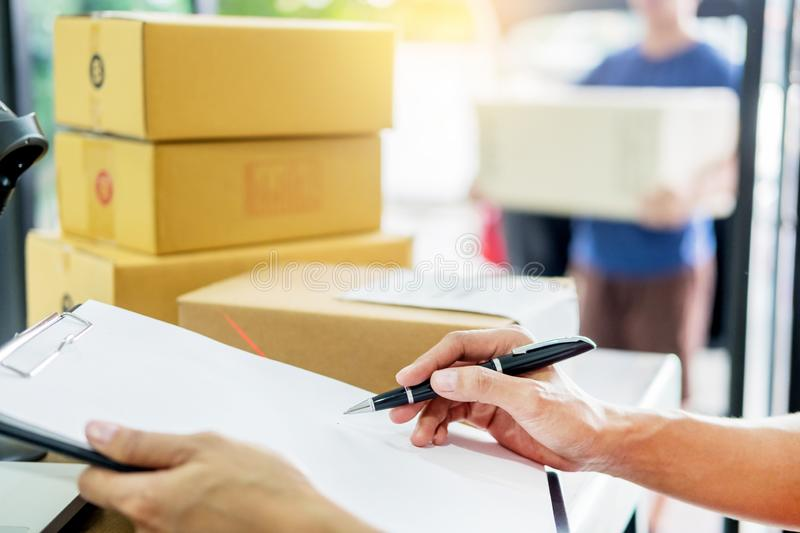 Courier hands Business woman work at home office checking parcel. Package box by keying machine track tools before ship and documents data royalty free stock image