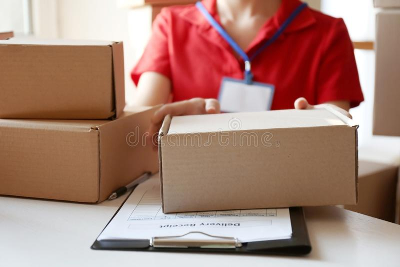 Courier hands giving packaged parcel. At table royalty free stock images