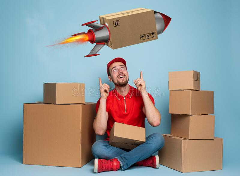 Courier is happy because boxes are delivery fast like a rocket. Studio on cyan background stock image