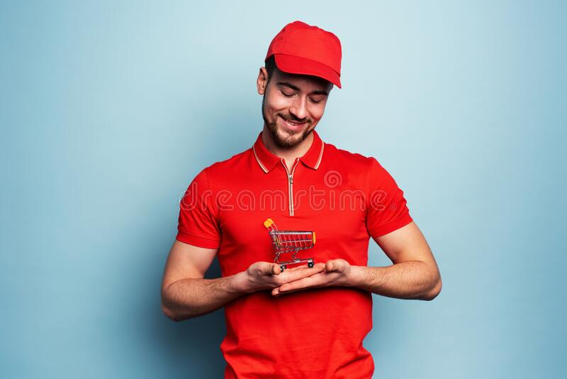 Courier man has care of parcel to deliver. Cyan background royalty free stock image