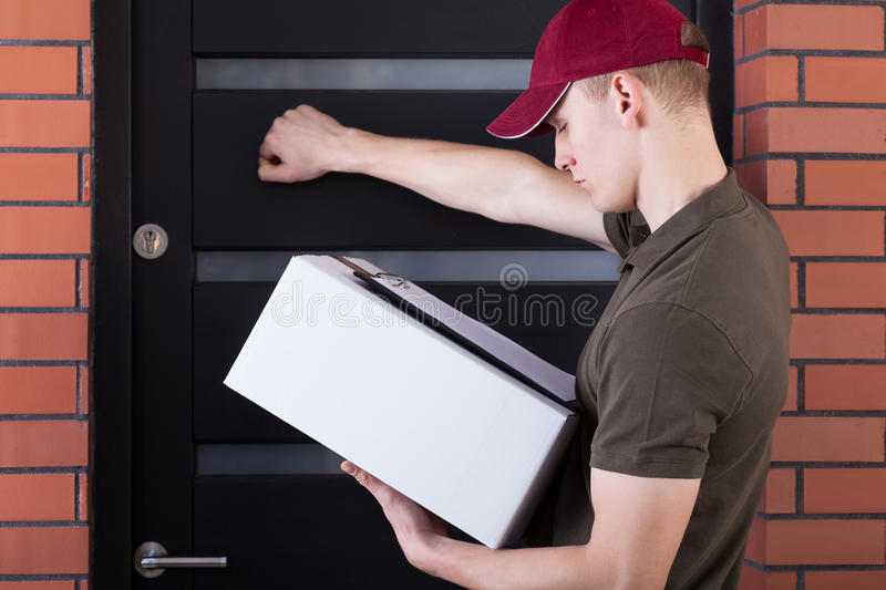 Courier knocking on customer's door. Courier knocking on a customer's door, horizontal royalty free stock image