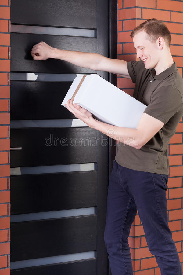 Courier knocking on doors. And holding order stock photography