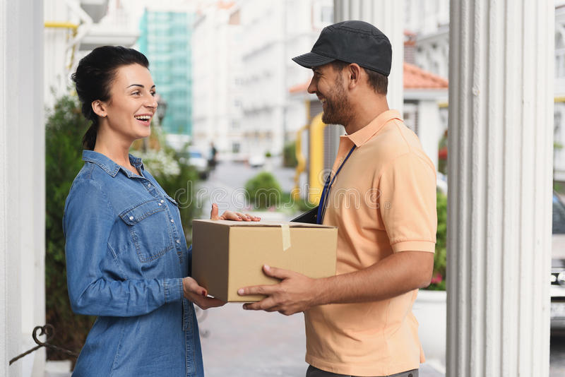 Courier making delivery to beautiful woman royalty free stock photography