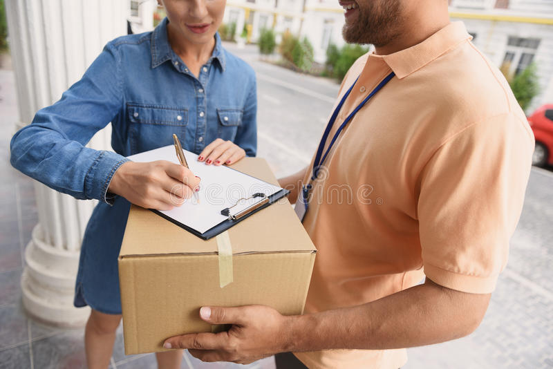 Courier making delivery to beautiful woman stock image