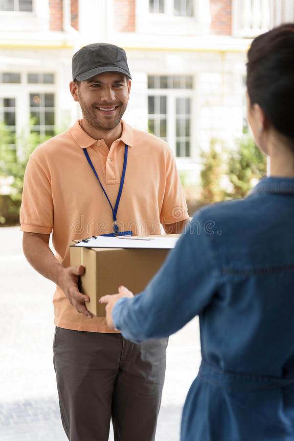 Courier making delivery to beautiful woman stock images