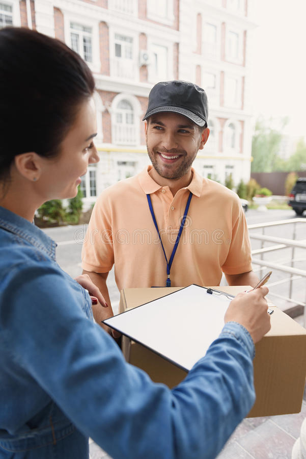 Courier making delivery to beautiful woman royalty free stock images