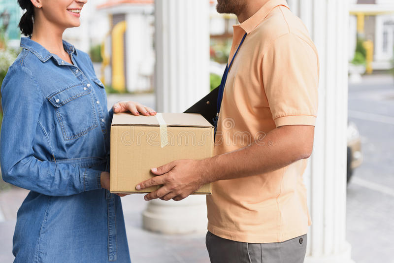Courier making delivery to beautiful woman stock photography