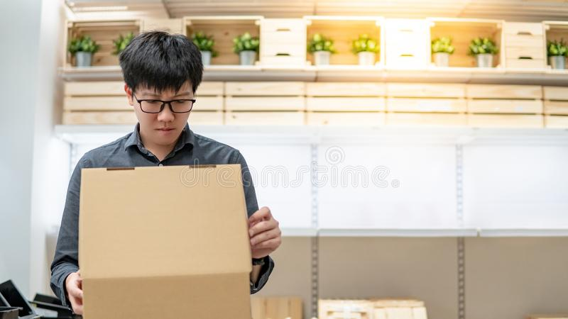 Courier man carrying box shopping in warehouse stock photo