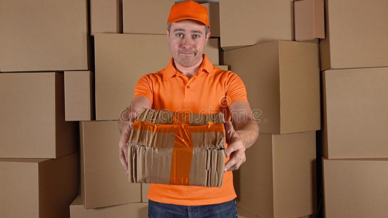 Courier in orange uniform delivering damaged parcel to customer. Brown cartons background. Flaw and unprofessional work. Courier in orange uniform delivering stock photos
