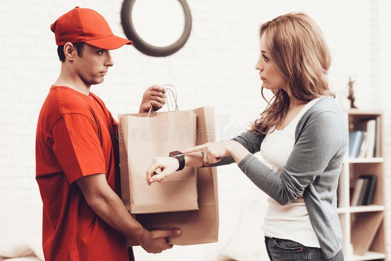 Courier with Packages and Displeased Girl in Room. Courier Delivery. Arab Deliveryman. Woman with Packge. White Interior. Deliveryman Arab Nationality. Courier stock photography