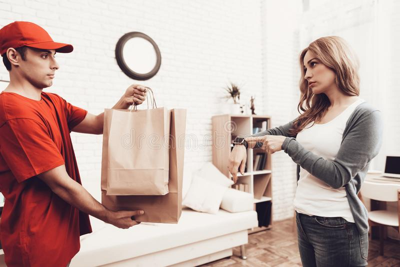 Courier with packages and girl with clock on arm. Courier Delivery. Arab Deliveryman. Woman with Packge. White Interior. Deliveryman Arab Nationality. Courier stock images