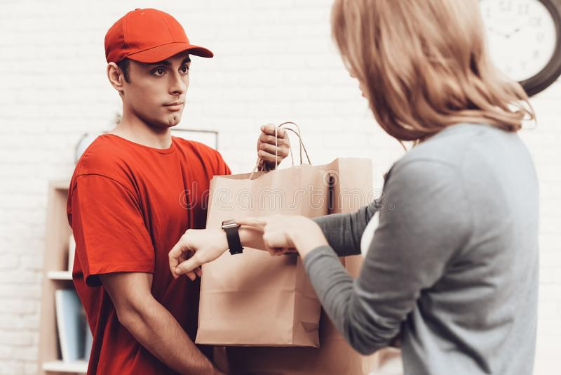 Courier with Packages and Girl with Clock on Arm. Courier Delivery. Arab Deliveryman. Woman with Packge. White Interior. Deliveryman Arab Nationality. Courier royalty free stock photography