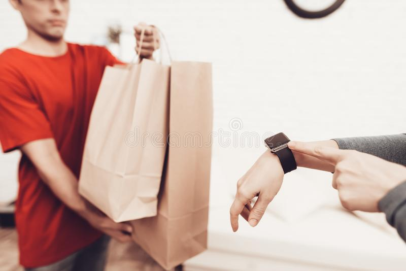 Courier with Packages and Woman with Clock on Arm. Courier Delivery. Arab Deliveryman. Woman with Packge. White Interior. Deliveryman Arab Nationality. Courier royalty free stock image