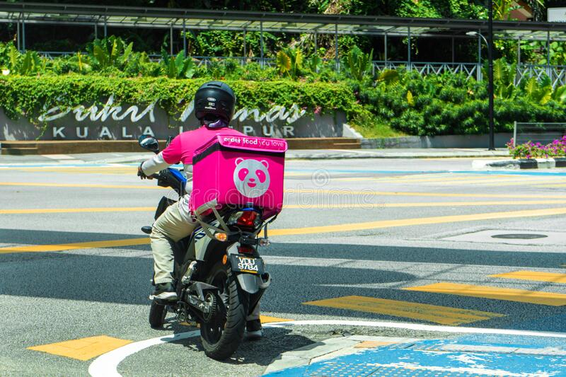 Courier of a popular food delivery service in Malaysia on a bike. Food ordering home.  stock photos