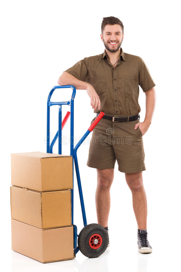 Courier posing with a push cart. Happy delivery man or mover standing relaxed close to push cart. Full length studio shot isolated on white royalty free stock image