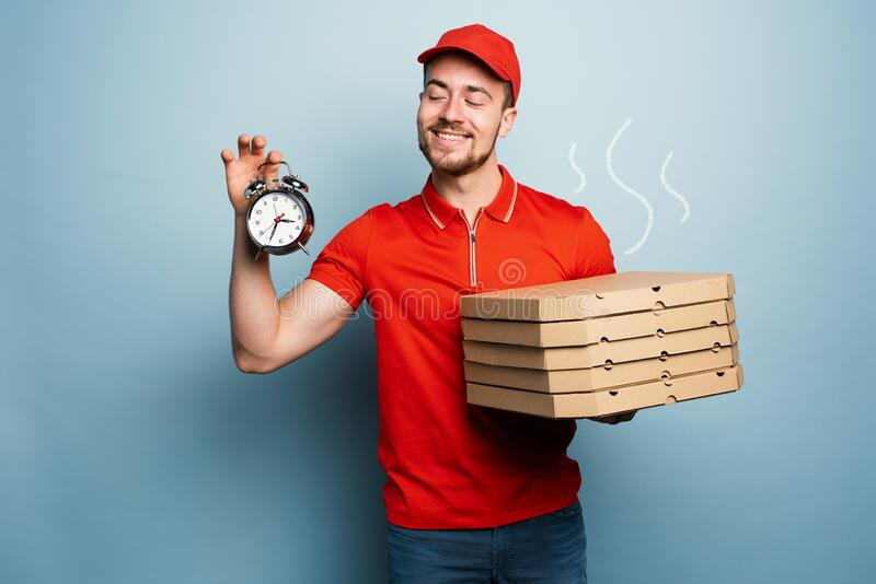 Courier is punctual to deliver quickly pizzas. Cyan background stock photo