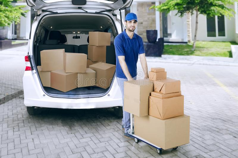 Courier pushing a dolly with packages. Handsome courier pushing a dolly with a pile of packages near the van royalty free stock image