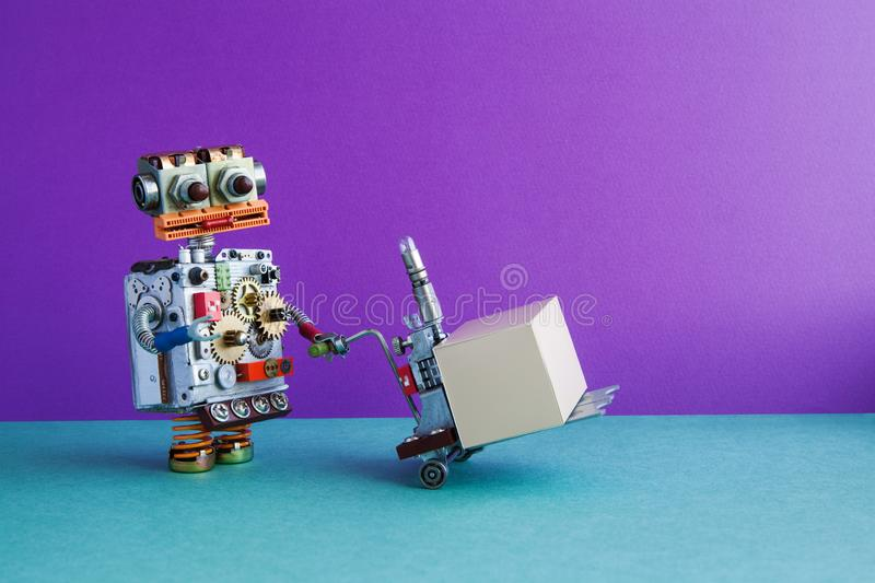 Courier robot moving pushcart with gray box parcel. Purple wall, green floor background. Copy space stock photos