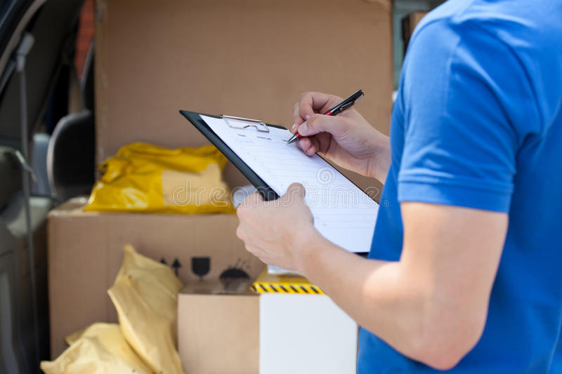 Courier's hand writing on clipboard stock image