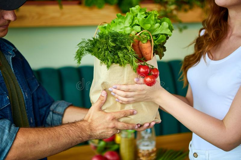 Courier service worker delivering fresh food, giving shopping bag to a happy woman client on the kitchen at home. Online grocery royalty free stock image
