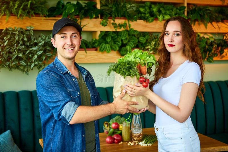 Courier service worker delivering fresh food, giving shopping bag to a happy woman client on the kitchen at home. Online grocery. Courier service worker stock image