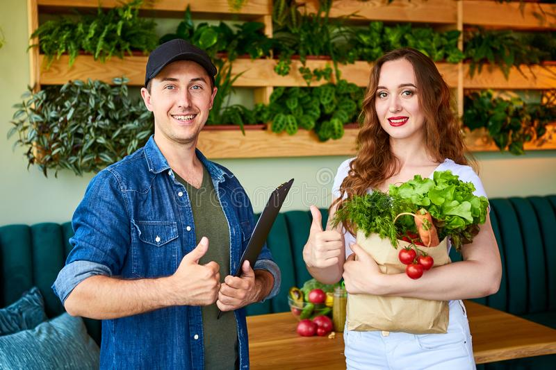 Courier service worker delivering fresh food, giving shopping bag to a happy woman client on the kitchen at home. Online grocery. Courier service worker stock photos