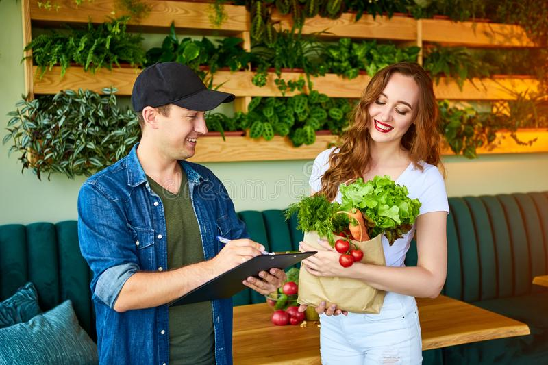 Courier service worker delivering fresh food, giving shopping bag to a happy woman client on the kitchen at home. Online grocery. Courier service worker stock images