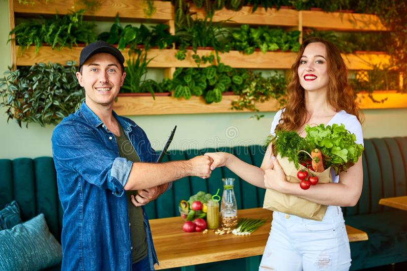 Courier service worker delivering fresh food, giving shopping bag to a happy woman client on the kitchen at home. Online grocery. Shopping from the internet stock photos