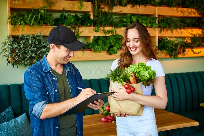 Courier service worker delivering fresh food, giving shopping bag to a happy woman client on the kitchen at home. Online grocery. Courier service worker stock photography